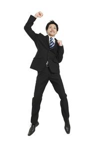 ジャンプする笑顔のビジネスマンの写真素材 [FYI01294341]