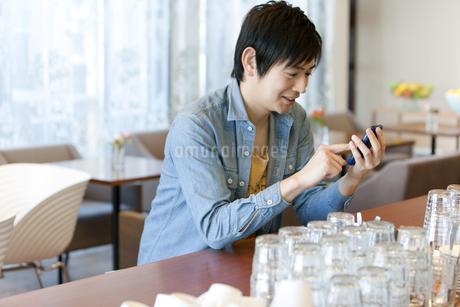 カフェでスマートフォンを操作する男性の写真素材 [FYI01294735]