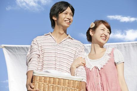 洗濯物を干す若いカップルの写真素材 [FYI01295088]