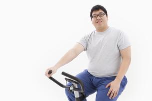 エアロバイクに乗る肥満男性の写真素材 [FYI01295249]