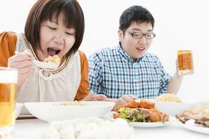 複数の料理と肥満カップルの写真素材 [FYI01295269]