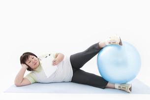 横になりタブレットPCを持つ肥満女性の写真素材 [FYI01295287]