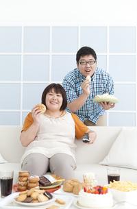 複数の菓子と肥満カップルの写真素材 [FYI01295313]