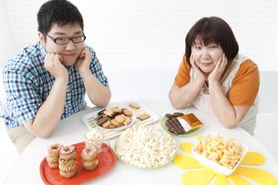 複数の菓子と肥満カップルの写真素材 [FYI01295338]