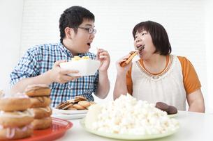 複数の菓子と肥満カップルの写真素材 [FYI01295351]
