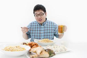 複数の料理と肥満男性の写真素材 [FYI01295354]
