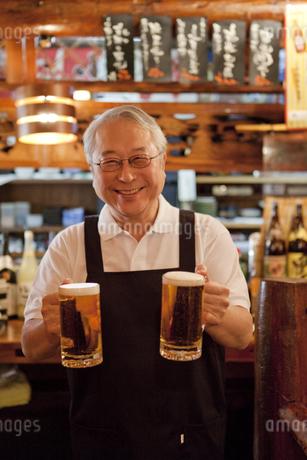 ビールを持っている笑顔の店員の写真素材 [FYI01295505]