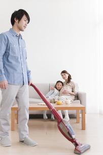 掃除機をかける父親と母娘の写真素材 [FYI01295729]