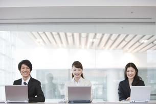 パソコンを操作するビジネスマンとビジネスウーマンの写真素材 [FYI01295781]