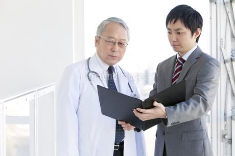 医師に書類を見せるビジネスマンの写真素材 [FYI01295816]