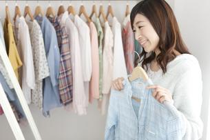 鏡の前で洋服を選ぶ女性の写真素材 [FYI01295918]