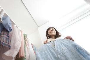 クローゼット前で洋服を選ぶ女性の写真素材 [FYI01295920]