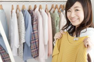 鏡の前で洋服を選ぶ女性の写真素材 [FYI01295938]