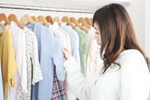 クローゼットで洋服を選ぶ女性の写真素材 [FYI01295948]