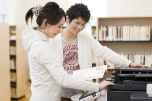コピー機の前で本を開くカップルの写真素材 [FYI01295956]