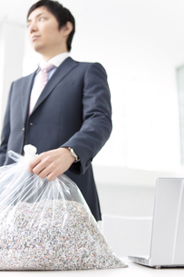 ゴミ袋を持つビジネスマンの写真素材 [FYI01296024]
