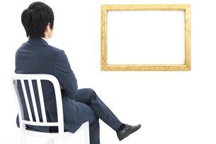 座って額を見るビジネスマンの写真素材 [FYI01296063]