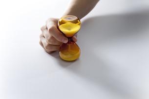 砂時計をつまむ手の写真素材 [FYI01296073]