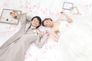 寝転ぶ新郎新婦と花びらの写真素材 [FYI01296138]