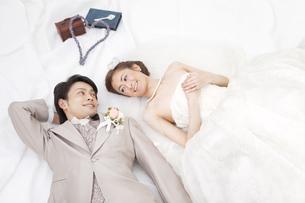 寝転ぶ新郎新婦の写真素材 [FYI01296182]