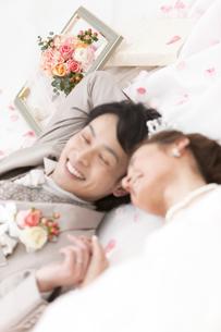 寝転ぶ新郎新婦と花びらの写真素材 [FYI01296190]