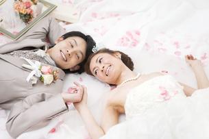 寝転ぶ新郎新婦と花びらの写真素材 [FYI01296215]