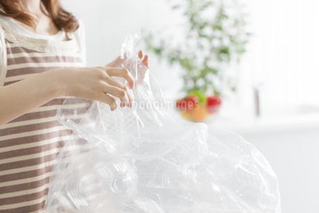 ペットボトルをゴミ袋に入れる女性の写真素材 [FYI01296329]