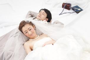 寝転ぶ新郎新婦の写真素材 [FYI01296354]