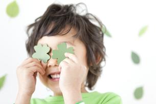 四つ葉のクローバーで遊ぶ男の子の写真素材 [FYI01296374]