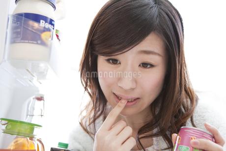 冷蔵庫で指をくわえる女性の写真素材 [FYI01296418]