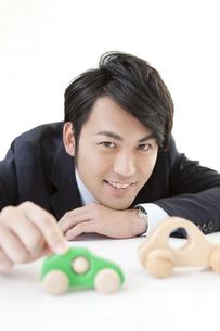 おもちゃの車に触れるビジネスマンの写真素材 [FYI01296483]