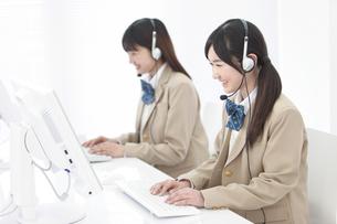 インカムをつけてパソコンをする女子高生2人の写真素材 [FYI01296573]