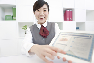 タブレットPCを持っている制服を着た女性の写真素材 [FYI01296662]
