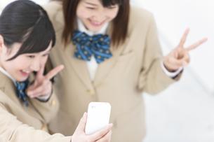 携帯で写真を撮る女子高生2人の写真素材 [FYI01296676]