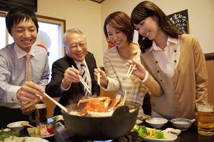 鍋を囲んでいるビジネスマン4人の写真素材 [FYI01296789]