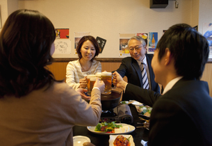 ビールで乾杯しているビジネスマン4人の写真素材 [FYI01296827]