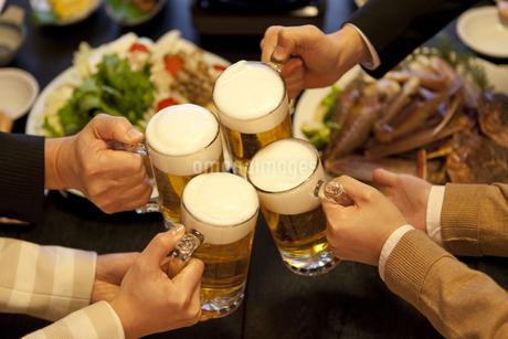 ビールで乾杯しているビジネスマン4人の写真素材 [FYI01296828]