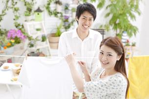 洗濯物を干すカップルの写真素材 [FYI01296833]
