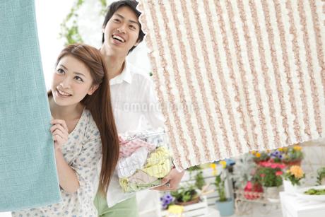 洗濯物を干すカップルの写真素材 [FYI01296837]