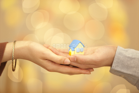 家の模型を持つ男女の手の写真素材 [FYI01297001]