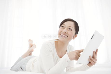 タブレットPCを持って寝転ぶ女性の写真素材 [FYI01297041]