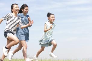 笑顔で走る女の子3人の写真素材 [FYI01297114]
