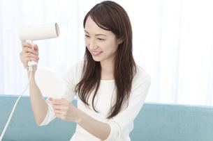 ドライヤーで髪を乾かす女性の写真素材 [FYI01297216]