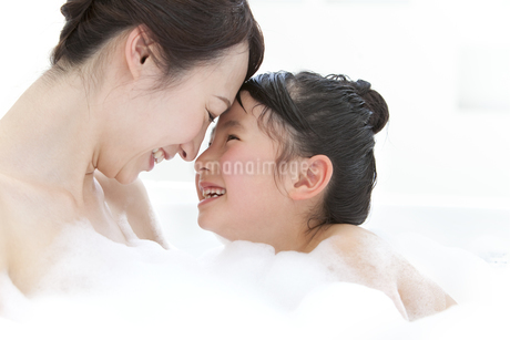 泡風呂に入る笑顔の親子の写真素材 [FYI01297218]