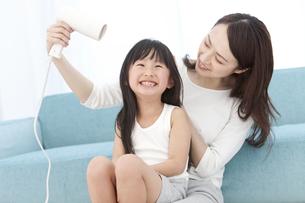母親に髪を乾かしてもらう女の子の写真素材 [FYI01297219]