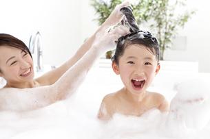 母親にシャンプーしてもらう女の子の写真素材 [FYI01297221]