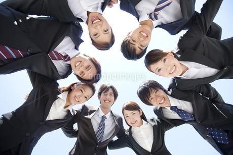 円陣を組むビジネスマンとビジネスウーマンの写真素材 [FYI01297450]