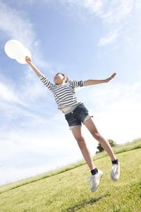 風船を持ってジャンプしている女の子の写真素材 [FYI01297818]