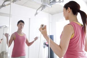 ジムで鏡に向かって運動をする女性の写真素材 [FYI01298070]