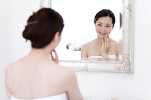 鏡に向かう笑顔の女性の写真素材 [FYI01298132]